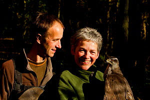 Rose and Lloyd Buck, professional bird handlers and trainers, holding adult female Goshawk (Accipiter gentilis) Somerset, UK, January 2013. Captive, occurs throughout much of the Northern Hemisphere.  -  John Waters