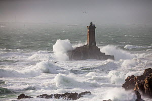 Waves lashing La Vieille ('The Old Lady') Lighthouse during winter storm, Plogoff, Finistere, Brittany, France. - Christophe Courteau
