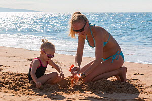 Mother and daughter playing with a spade on the beach. Biarritz, Aquitaine, France, September 2014. Model released.  -  Christophe Courteau