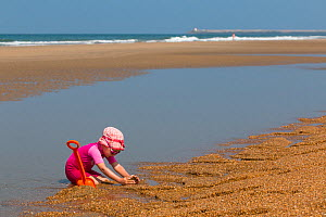 Young girl playing on the beach with a spade. Biarritz, Aquitaine, France, September 2014. Model released.  -  Christophe Courteau