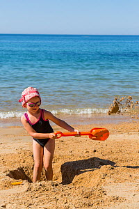 Young girl with plastic spade digging hole on the beach. Biarritz, Aquitaine, France, September 2014. Model released.  -  Christophe Courteau