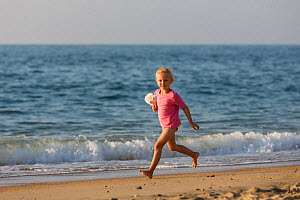 Young girl running along beach with soft toy. Biarritz, Aquitaine, France, September 2014. Model released. - Christophe Courteau