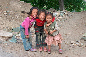 Group of local children smiling, near Lantsang Mekong river, Kawakarpo Mountain, Meri Snow Mountain National Park, Yunnan Province, China.  -  Dong Lei