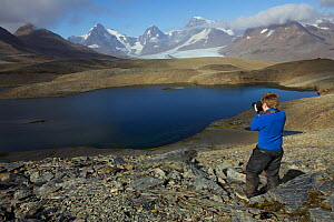 Russell Laman photographing Crean Lake on the hike between Fortuna Bay and Stromness, retracing part of Shackleton's route. South Georgia, February 2011. Model released.  -  Tim  Laman