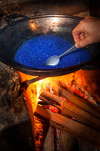 Photographer heating silica gel over camp fire in rainforest to restore its desiccating properties. The high humidity of the rainforest can fog camera lenses and lead to mould growth, so silica gel is...  -  Alex  Hyde