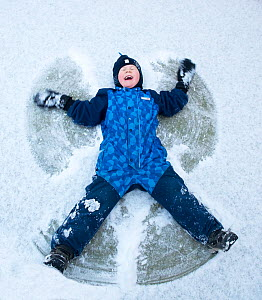 Child lying in the snow creating snow angel, Norway, January 2014. Model released. - Pal Hermansen