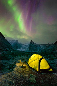 Aurora Borealis over yellow tent lit from within and mountainous scenery, Arrigetch Peaks, Gates of the Arctic National Park, Brooks Range, Alaska, USA, August 2014. - Floris  van Breugel