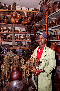 Interior of a toursit shop in Addis Ababa with seller holding a Coptic cross that is for sale. Shop features various items, paraphernalia, such as Coptic crosses, headrests, bottle gourds, a stuffed c...  -  Constantinos Petrinos