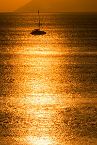 Sunset reflected on the surface of the Aegean Sea on a calm day with a sailing boat, Evia Island, Greece. July 2014. - Constantinos Petrinos