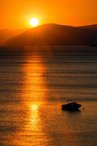 Sunset reflected on the surface of the Aegean Sea on a calm day with a speedboat, Evia Island, Greece. July 2014. - Constantinos Petrinos