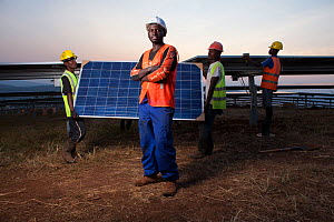 Technicians installing panels in one of East Africa's largest Solar farms, Rwamagana District, Rwanda. July 2014. Model released.  -  Tom  Gilks