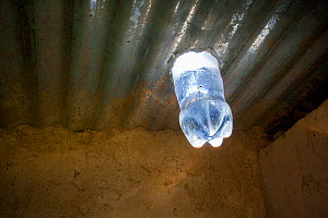 Water filled bottle fixed into a tin roof, dispersing sunlight and acting as a natural lightbulb. Kenya. April 2013.  -  Tom  Gilks