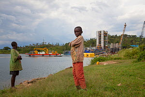Two children standing in front of Kivuwatt biogas plant under construction. The plant will remove methane from the waters of Lake Kivu and power three genrators to produce 26MW of electricity. Kibuye,...  -  Tom  Gilks