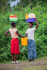 Women talking to each other whilst carrying plastic baskets on their heads, Mfangano Island, Lake Victoria, Kenya, February 2013.  -  Tom  Gilks