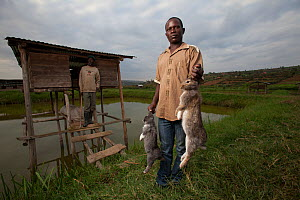 Rwandan farmers with rabbits, outside their hutches which sit over a fish-pond, Rwanda, June 2014.  -  Tom  Gilks