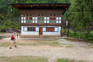 Hiker on the Jhomolhari Trek, passing by a traditional farm house, Paro River Valley.  Bhutan, October 2014. Model released.  -  Kirkendall-Spring