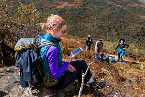 Woman using a mobile phone miles away from any city along the Jhomolhari Trek.  Bhutan, October 2014. Model released.  -  Kirkendall-Spring