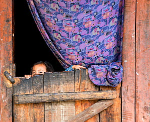 Young girl looking out of a doorway, Paro River Valley. Bhutan, October 2014.  -  Kirkendall-Spring