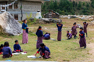 Children in school playground, with teacher standing to the side,  Paro River Valley. Bhutan, October 2014. - Kirkendall-Spring