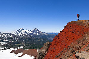 Hiker on the crater rim of Broken Top, and view towards Middle and North Sister. Three Sisters Wilderness, Deschutes National Forest.  Oregon, USA, July 2014.  Model released. - Kirkendall-Spring