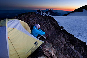 Woman camping on the crater rim of South Sister, Three Sisters Wilderness, Deschutes National Forest.  Oregon, USA, July 2014. Model released.  -  Kirkendall-Spring