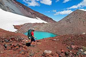 Hiker passing a small lake part way to the summit of South Sister, Three Sisters Wilderness, Deschutes National Forest, Oregon, USA, July 2014. Model released.  -  Kirkendall-Spring