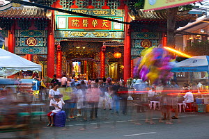 People moving around in front of a shrine, China Town area of Bangkok. Thailand, September 2014. - Kirkendall-Spring