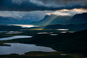 Dark clouds and shaft of sunlight with Stuor Tuvva lake (foreground) and the Patsasj (Petsasj) lake (background), view from Vietovare Mountain. From left to right, mountains Nieras, Alddas and Paljasj... - Orsolya  Haarberg