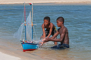 Young Vezo boys, playing with toy boat (pirogue) learning the necessary skills to sail as fisherman, Morondave, Madagascar. November 2014. - Bernard Castelein