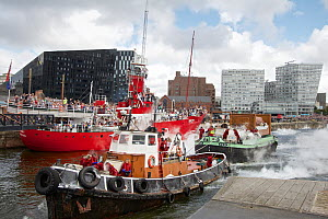 Giant marionettes Grandmother, Little Girl and dog 'Xolo' aboard the barge 'Hen' pulled by the tug Seaport Alpha, passing the Canning Dock lock. Liverpool, Merseyside, United Kingdom, July 2014. All n... - Graham  Brazendale