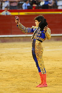 Matador with ear of bull, a 'trofeo' or trophy for a good performance, Plaza de Toros, Valencia, Spain. July 2014. - Barry Bland