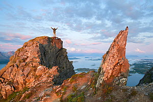 View from Mt Donnamannen and man standing on rock with arms raised, Helgeland, Nordland, Norway, July, 2009.  -  Erlend  Haarberg