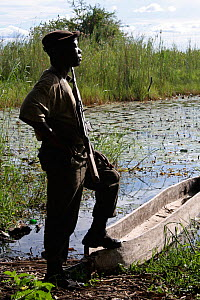 Park ranger with one foot resting on  dugout canoe, Sioma Nqwezi Park, Zambia. November 2010.  -  Steve O. Taylor (GHF)