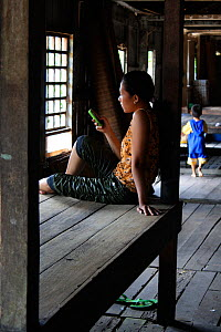 Dayak woman on mobile phone, in longhouse, Pontianka, West Kalimantan, Indonesian Borneo. June 2010. - Steve O. Taylor (GHF)