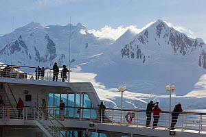Cruise ship and passengers in front of snow covered mountains, Paradise Bay, Antarctica, January. - Michael Hutchinson