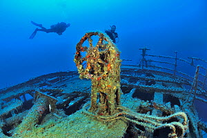 Divers by steering wheel of the Imperial Eagle wreck, a ferry sunk in 1999 in Qawra Point as an artificial reef, Malta, Mediterranean Sea. June 2014. - Pascal Kobeh