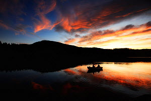 Fishing boat near Vassfaret mountain valley, silhouetted at sunset, Norway, September 2009.  -  Ole  Jorgen Liodden