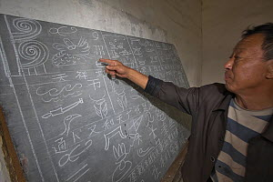 Man pointing at Naxi pictograph character written on blackboard, Yunnan, China - Dong Lei