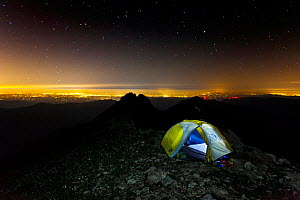 Campsite at night with city lit up  below, Three Fingers Lookout, Boulder River Wilderness, Mount Baker-Snoqualmie National Forest, Washington, USA. August 2014.  -  Kirkendall-Spring