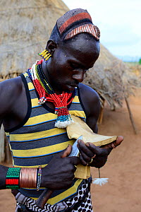 Hamer man in traditional clothes and ornaments carving wood. Territory of the hamer tribe. Lower Omo Valley. Ethiopia, November 2014 - Enrique Lopez-Tapia