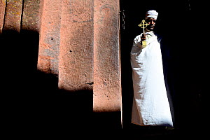 Priest in traditional white robes and turban, holding a gold cross. Bet Giyorgis Church, Lalibela. UNESCO World Heritage Site. Ethiopia, December 2014. - Enrique Lopez-Tapia
