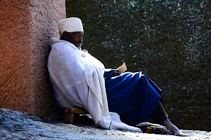 Christian worshiper in traditional white robes, resting against wall, Bet Medhane Alem (part of the northwestern group of churches in Lalibela). UNESCO World Heritage Site. Lalibela. Ethiopia, Decembe...  -  Enrique Lopez-Tapia