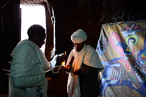 Devout Christian in traditional robess lighting candle in front of Bet Danaghel (part of the northwestern group of churches in Lalibela). UNESCO World Heritage Site. Lalibela. Ethiopia, December 2014.  -  Enrique Lopez-Tapia