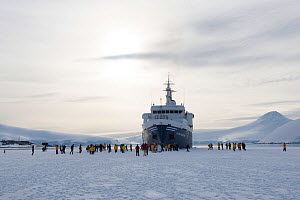 Tourists from the 'Clipper Adventurer' walking on winter fast ice at Port Lockroy, Goudier Island, Antarctic Peninsula. November, 2011. All non-editorial uses must be cleared individually.  -  Rick Price