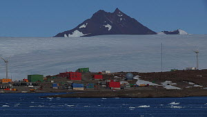 Mawson Station seen from a boat, with two wind turbines turning and mountains of the David Range in the background, Antarctica. - Fred  Olivier