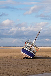 Small boat ashore at low tide on shore at Meols, Hoylake, Wirral, Merseyside, England UK. May 2015 All non editorial uses must be cleared individually. - Norma  Brazendale