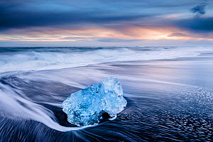 Ice on black volcanic sand beach with waves, Jokulsarlon, Southeast Iceland, February.  -  Ross Hoddinott
