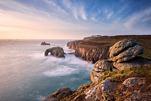 View towards Enys Dodnan Arch and the Armed Knight rock, Land's End, with Longships lighthouse in the distance, Cornwall, UK. March 2015.  -  Ross Hoddinott