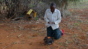 Man wafting a small charcoal fire to increase airflow, Kenya, 2014.  -  Steve O. Taylor (GHF)