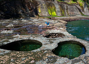 Woman exploring the tide pools north of Carmanah Point along the West Coast Trail in Pacific Rim national Park Reserve, British Columbia, Canada, May 2015.  Model released. - Kirkendall-Spring